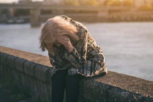 Stresset kvinde tager sig til hovedet grundet langtidsledighed
