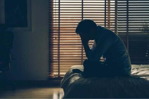 Person i mørkt rum tager sig til hoved grundet skizofreni