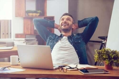 Smilende mand ved skrivevord besidder professionel selvbevidsthed