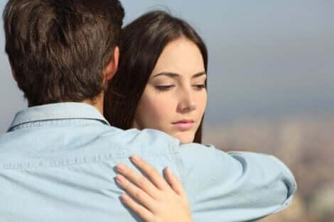 Bekymret kvinde krammer mand som symbol for at sætte en anden på en piedestal