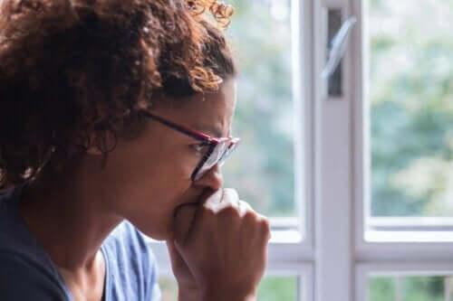 Bekymret kvinde ved vindue
