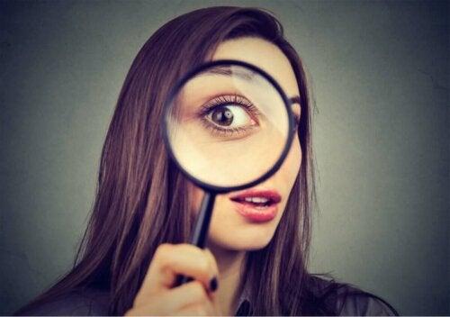 Kvinde, der kigger gennem forstørrelsesglas