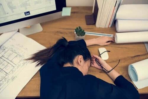 Kvinde, der ligger udmattet over skrivebord