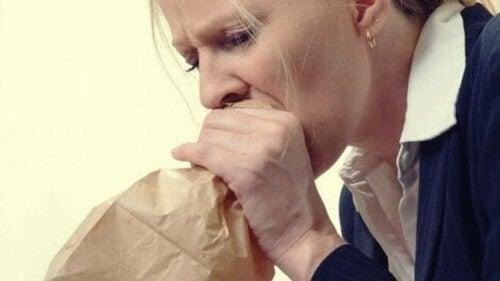 Kvinde trækker vejret gennem en papirspose