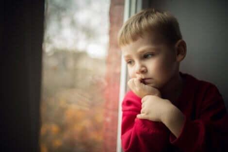 Lille dreng, der kigger ud af vindue