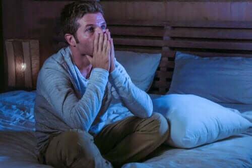 Mand, der sidder bekymret i seng