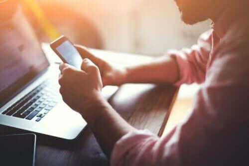 Person med computer og telefon i hånden