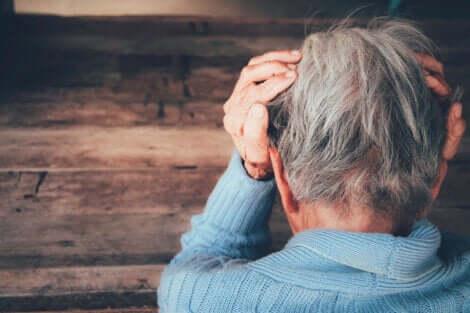 Ældre kvinde, der tager sig til hovedet