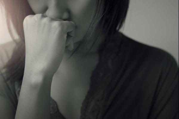 Kvinde holder knyttet næve ved sin mund
