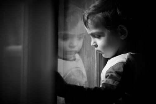 Trist pige ser ud af vindue