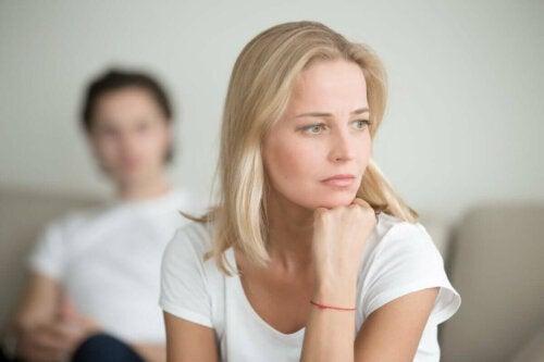 Fortvivlet kvinde med mand i baggrunden