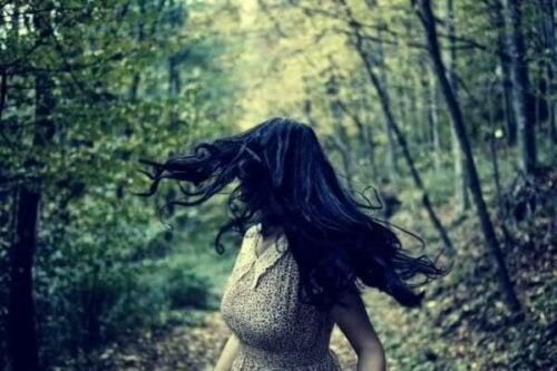 Kvinde, der kigger sig tilbage i skoven