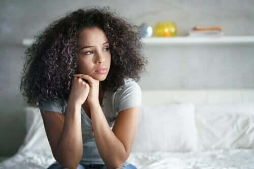 Kvinde, der sidder på seng og tænker