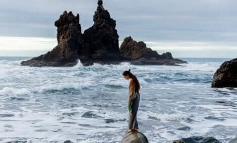 Kvinde, der står på sten ud mod havet