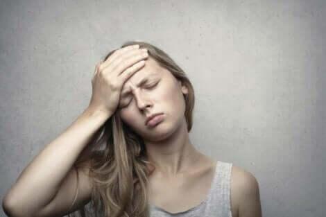 Kvinde med krisetræthed tager sig til hoved