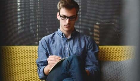 Mand, der skriver på en blok papir