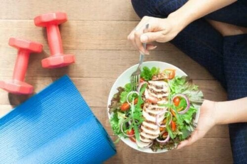 Person, der sidder på gulv med en skål salat