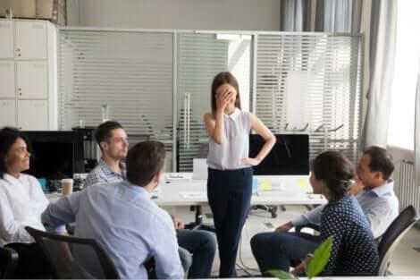 Pinlig berørt kvinde foran medarbejdere
