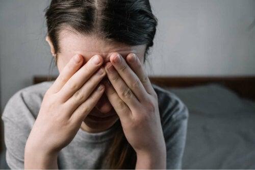 Stresset kvinde skjuler ansigt bag hænderne