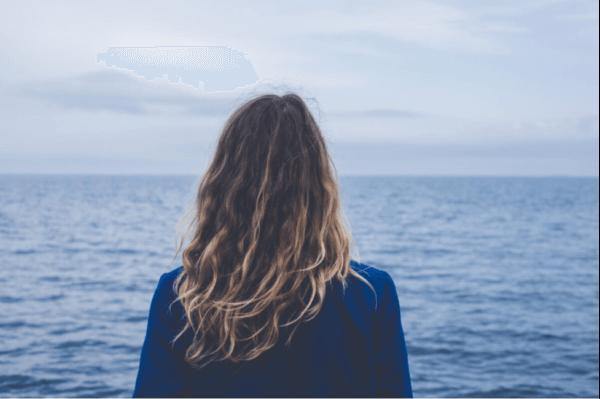 Kvinde, der ser ud over havet
