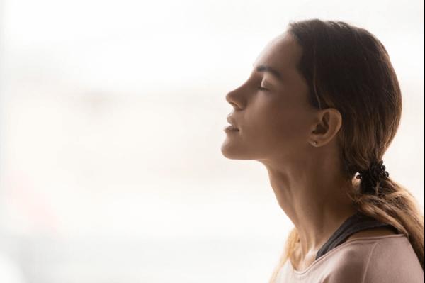 Kvinde med lukkede øjne laver åndedrætsteknikker
