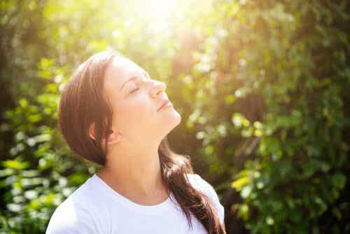 Kvinde står med lukkede øjne i solskin
