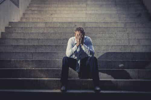 Mand sidder med hovedet i hænderne på en trappe