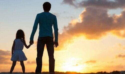 Far og datter hånd i hånd foran solnedgang