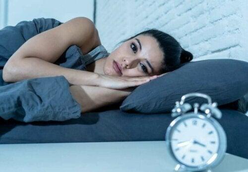 Kvinde ligger søvnløs i seng, selvom for lidt søvn skaber falske minder