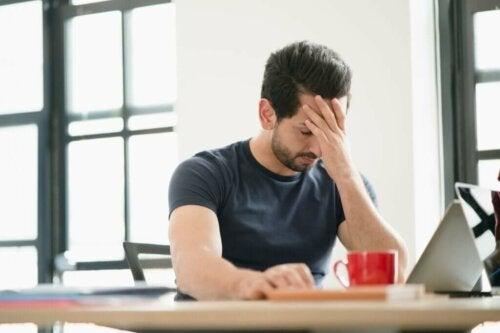 Mand har hovedpine grundet stressfaktorer på arbejdspladsen