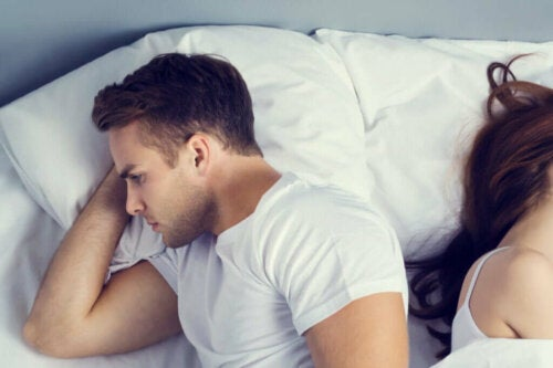 Mand og kvinde ligger med ryggen mod hinanden i en seng