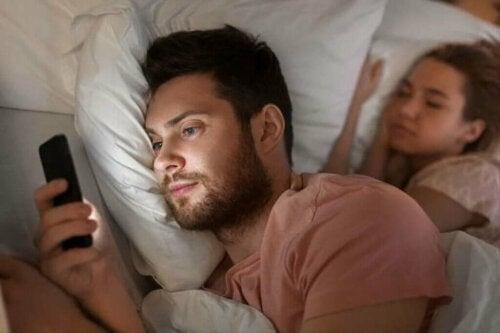 Par i seng, hvor manden bruger telefonen til digitalt utroskab