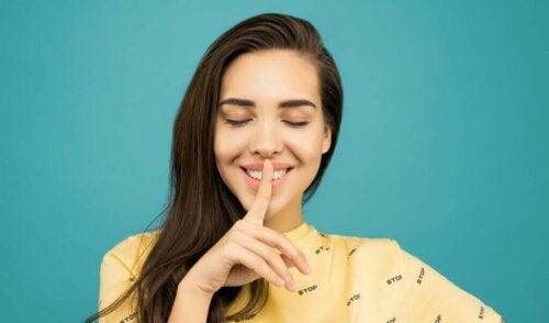 Smilende kvinde tysser ved at sætte fingeren op foran munden