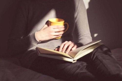 Person læser med te i hånden