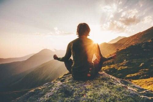 Person mediterer på toppen af et bjerg