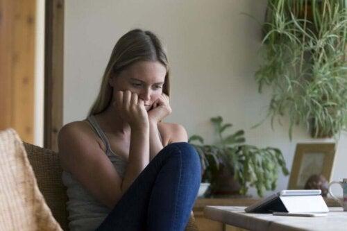Frustreret kvinde med telefon foran sig