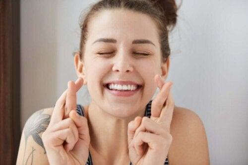 Smilende kvinde med krydsede fingre