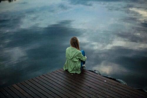 Kvinde sidder på bro ved sø