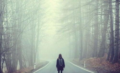 Kvinde står alene på vej i skov