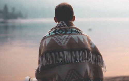 Mand med tæppe om sig sidder alene ved vand, da han ikke har lyst til at være social