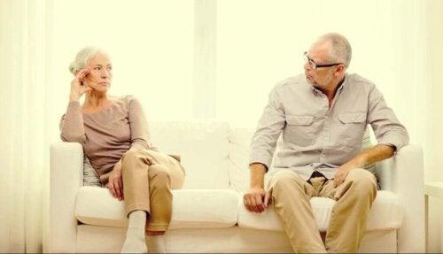 Ældre par sidder i sofa og ser på hinanden