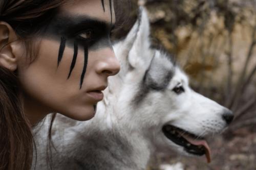 Denne vilde kvinde med sort maling i ansigtet og en ulv ved sin side